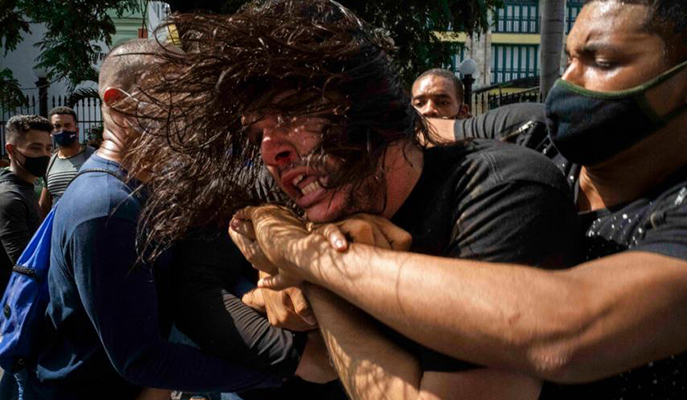 Officers detain a protester during a protest in Havana, Cuba