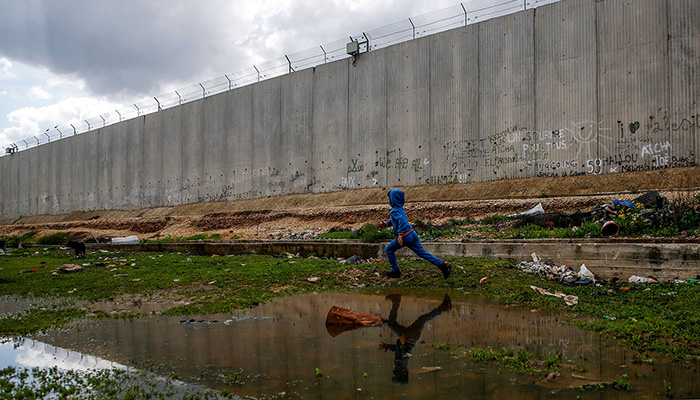 A boy dressed in blue runs through a muddy, garbage-strewn area next to a tall grey concrete wall topped with barbed wire and littered with graffiti. His reflection is shown in a muddy puddle on the ground.